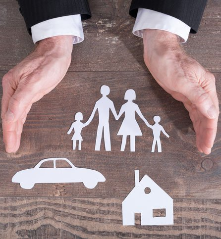 hands holding paper cutouts of a family, car and home